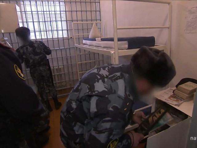 Trong khi phạm nhân tập thể dục, lính bảo vệ kiểm tra phòng giam và đồ cấm.