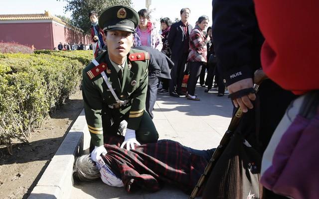 Cảnh sát bán quân sự bắt giữ một phụ nữ được cho là ném đơn kiện trước lối vào Tử  Cấm Thành ở Bắc Kinh, Trung Quốc.
