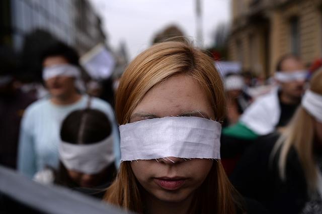 Các sinh viên cùng băng trắng che mắt tham gia biểu tình trên đường phố ở Sofia, Bulgaria.