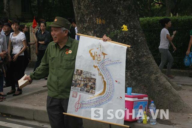 Ông Chính và bức vẽ bản đồ Việt Nam được bao phủ trên đó là lời bài hát Việt Nam quê hương tôi.