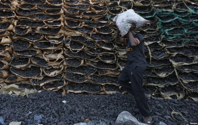 Công nhân vác một bao than hoa đi bán tại bãi than ở Jeddah, Ả-rập Xê-út.