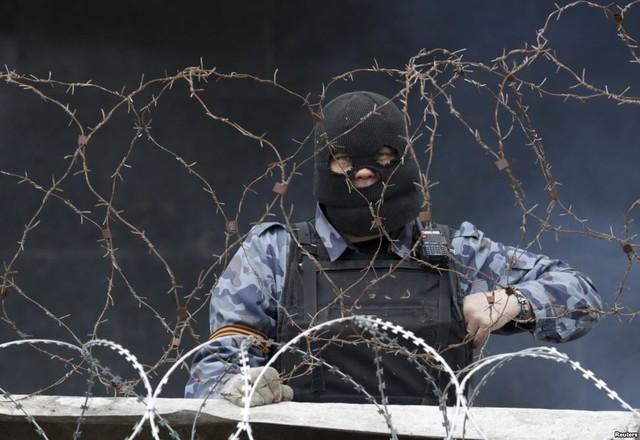 Một người tình ủng hộ Nga đứng bảo vệ tại hàng rào dây thép gai được dựng bên ngoài tòa nhà thị chính ở Donetsk, Ukraine.