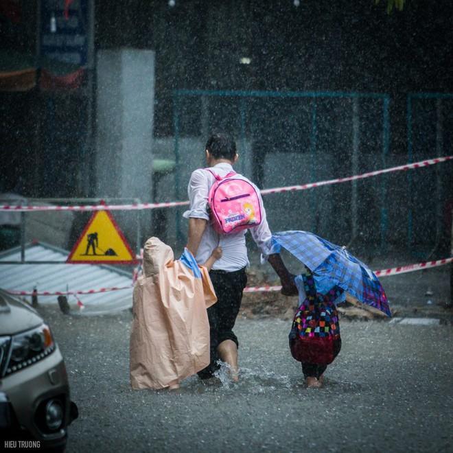Giữa cơn mưa lớn, hình ảnh 3 cha con khiến người ta xúc động - Ảnh 1.