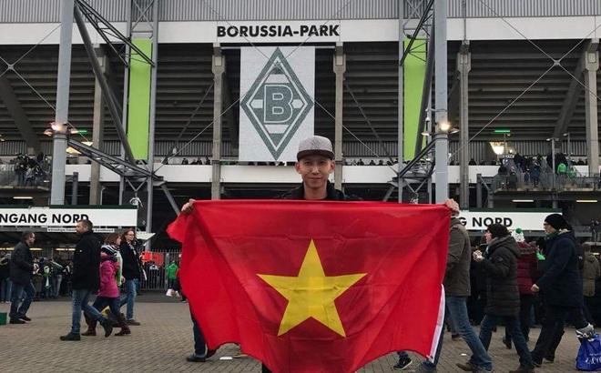 Trên khán đài SVĐ Borussia-Park, Nghiêm Xuân Tú khoe lá cờ đỏ sao vàng và chiếc áo đấu quen thuộc.