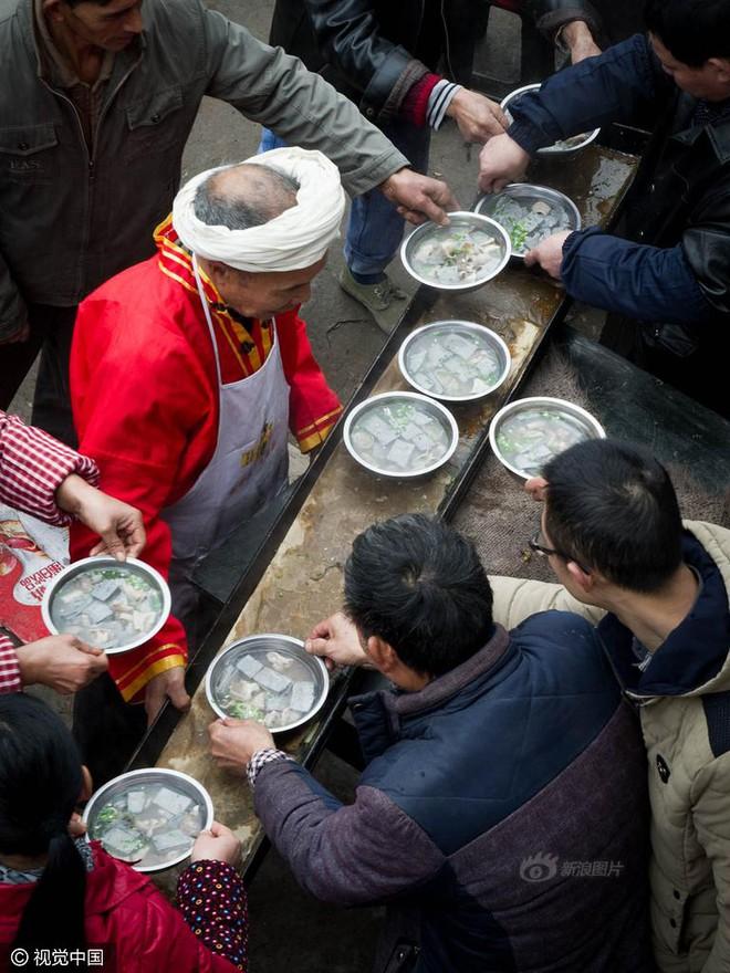 Chùm ảnh: Người đàn ông 38 năm chuyển thức ăn bằng đầu, đội 300.000 bát chưa 1 lần rơi - Ảnh 5.