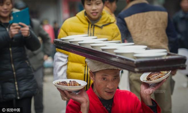 Chùm ảnh: Người đàn ông 38 năm chuyển thức ăn bằng đầu, đội 300.000 bát chưa 1 lần rơi - Ảnh 8.
