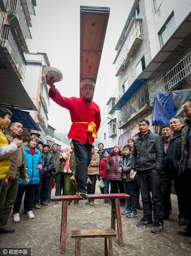 Chùm ảnh: Người đàn ông 38 năm chuyển thức ăn bằng đầu, đội 300.000 bát chưa 1 lần rơi - Ảnh 9.