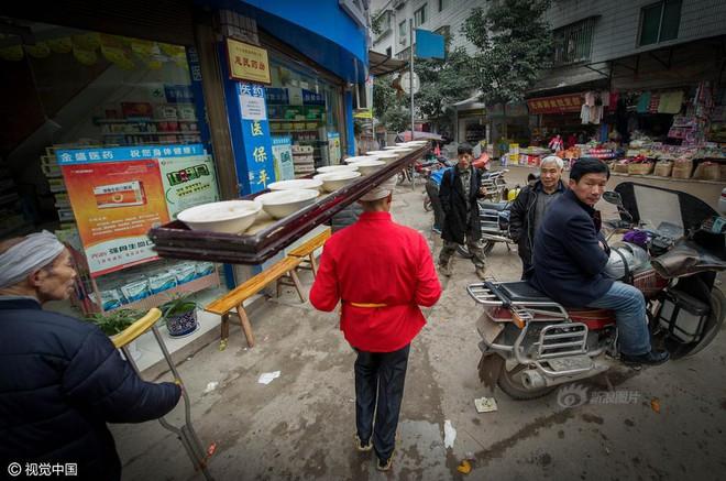 Chùm ảnh: Người đàn ông 38 năm chuyển thức ăn bằng đầu, đội 300.000 bát chưa 1 lần rơi - Ảnh 10.