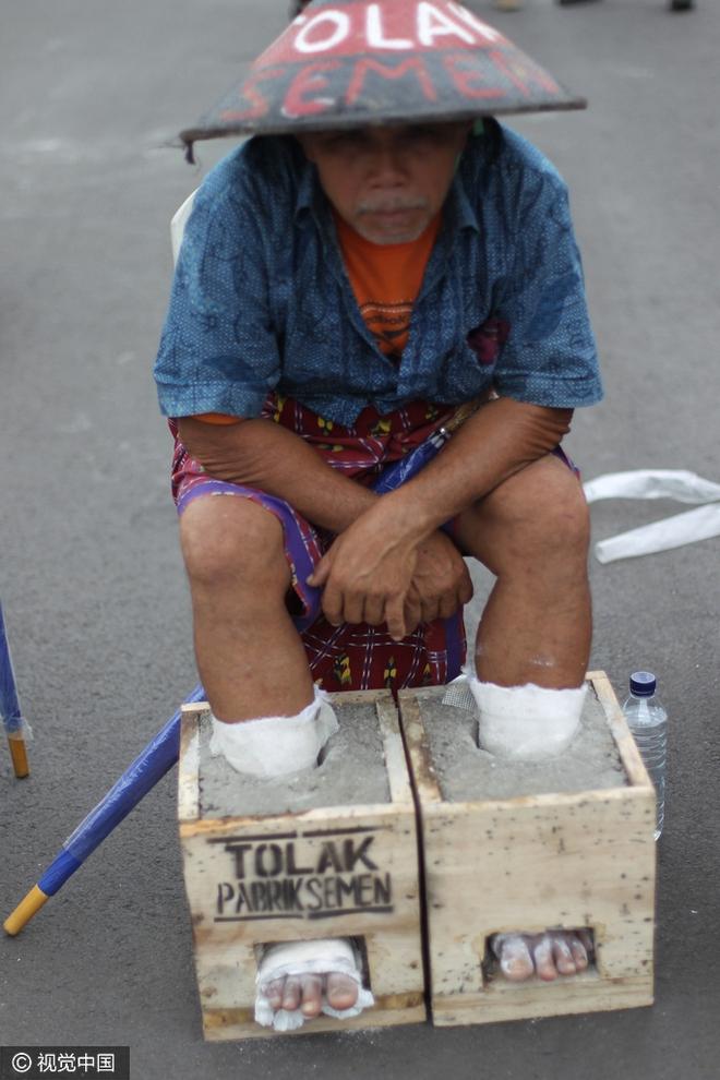 Đằng sau hình ảnh nông dân Indonesia đồng loạt chôn chặt chân trong xi măng - Ảnh 2.