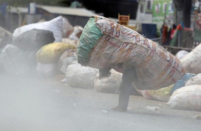 24h qua ảnh: Em bé nhọc nhằn cõng bao tải phế liệu mưu sinh ở Campuchia - Ảnh 3