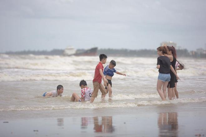 Bất chấp sóng to, gió lớn, nhiều người vẫn ra tắm ở biển Cửa Lò - Ảnh 1.