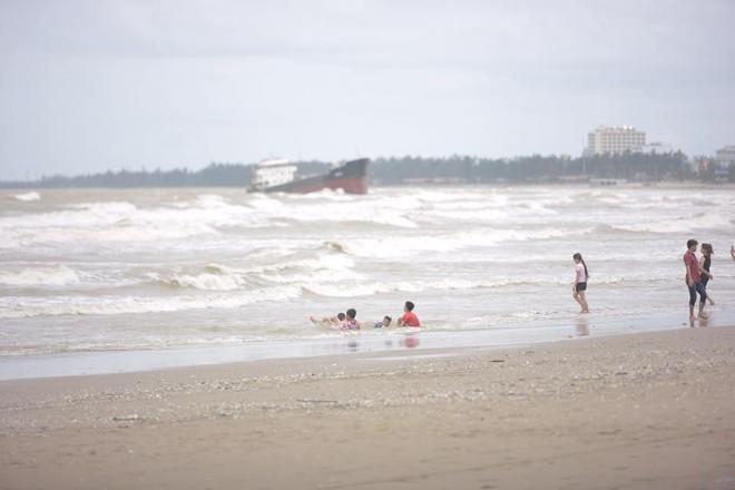 Bất chấp sóng to, gió lớn, nhiều người vẫn ra tắm ở biển Cửa Lò - Ảnh 3.