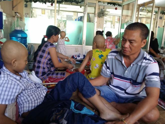 Anh Trần Tấn Quốc cùng con trai của mình tại bệnh viện Ung Bướu.
