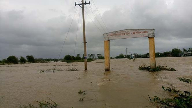 Đường phố Bình Định chìm trong biển nước, người dân dùng máy cày vượt lũ - Ảnh 1.