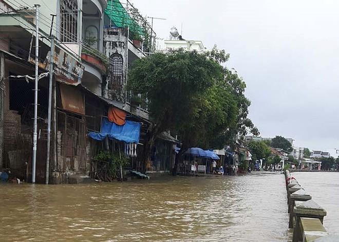Đường phố Bình Định chìm trong biển nước, người dân dùng máy cày vượt lũ - Ảnh 2.
