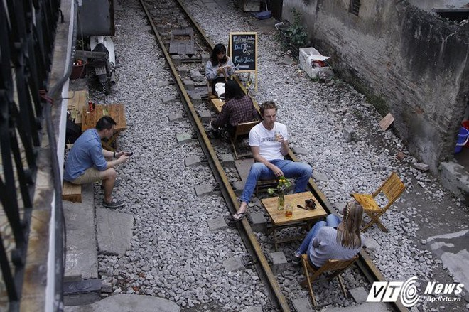 Ảnh: Khách nước ngoài thích thú ngồi uống cà phê trên đường ray tàu hỏa ở Hà Nội - Ảnh 3.