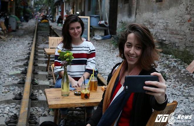 Ảnh: Khách nước ngoài thích thú ngồi uống cà phê trên đường ray tàu hỏa ở Hà Nội - Ảnh 7.