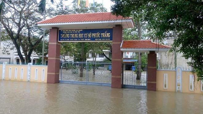 Đường phố Bình Định chìm trong biển nước, người dân dùng máy cày vượt lũ - Ảnh 8.