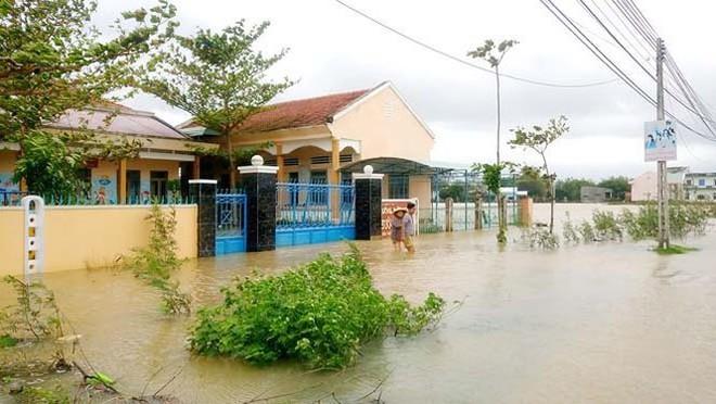 Đường phố Bình Định chìm trong biển nước, người dân dùng máy cày vượt lũ - Ảnh 9.