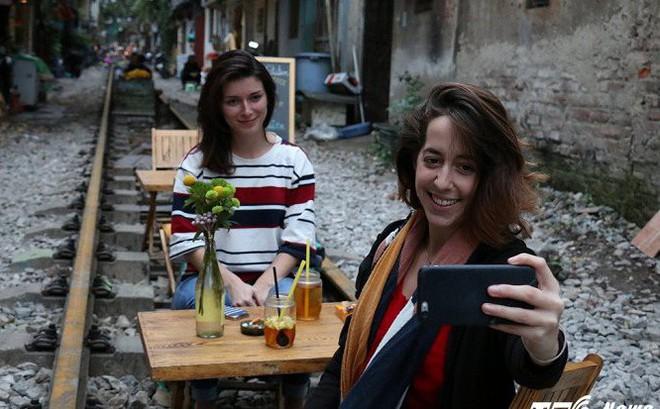 Ảnh: Khách nước ngoài thích thú ngồi uống cà phê trên đường ray tàu hỏa ở Hà Nội