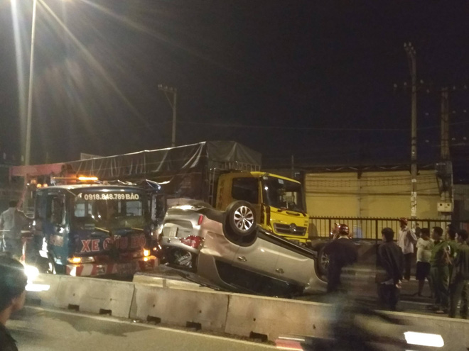 Xe tải ủi ô tô lật ngửa trên đường, 4 người trong xe la hét cầu cứu ở Sài Gòn - Ảnh 1.