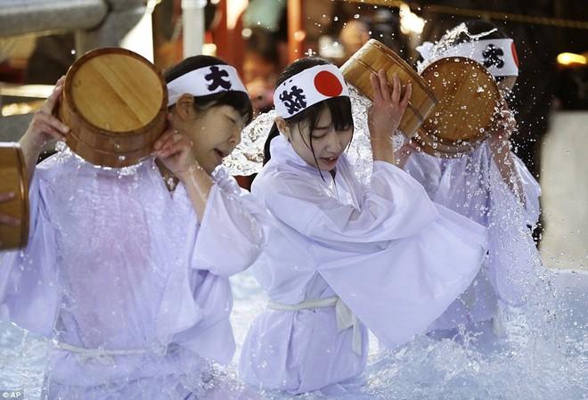 24h qua ảnh: Cậu bé Hàn Quốc vui sướng ngậm cá hồi sống trong lễ hội băng - Ảnh 2.