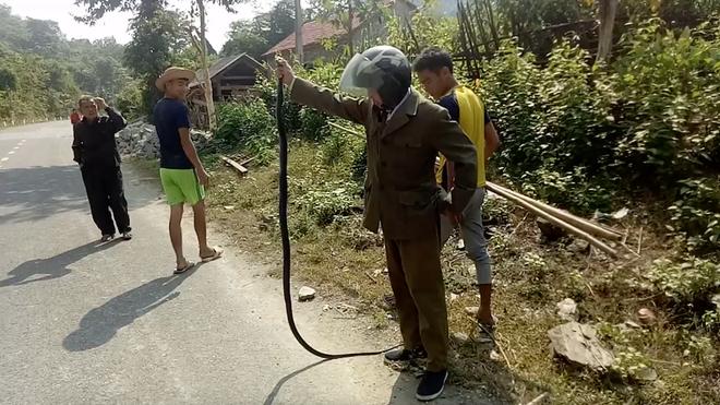 Gặp rắn độc dài 2m bò ngang quốc lộ, người đàn ông vứt xe máy xuống bắt bằng tay - Ảnh 2.