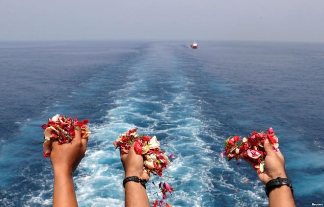 24h qua ảnh: Thân nhân của hành khách trên máy bay rơi thả cánh hoa xuống biển - Ảnh 4.