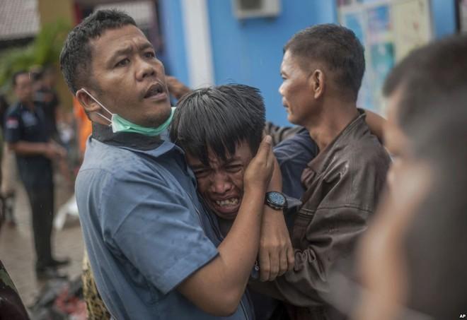 24h qua ảnh: Người đàn ông bật khóc khi thấy xác thân nhân sau sóng thần - Ảnh 3.