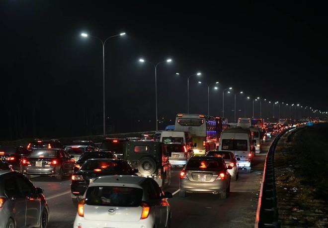 Tối mùng 4 Tết, ô tô xếp hàng dài ở 2 đầu trạm thu phí Pháp Vân về Hà Nội - Ảnh 1.