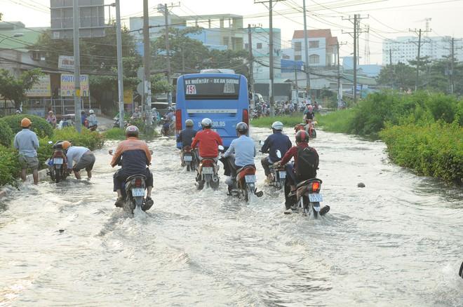 Nước dâng ngập lút bánh xe trên nhiều tuyến đường ở Sài Gòn - Ảnh 2.
