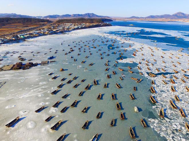 24h qua ảnh: Đoàn thuyền đánh cá mắc kẹt trên mặt nước đóng băng ở Trung Quốc - Ảnh 2.