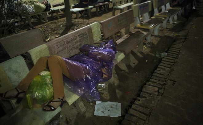 Người phụ nữ mặc áo mưa, ngủ qua đêm trên ghế đá chờ xin ấn đền Trần
