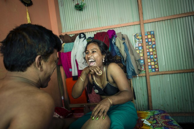 Bonna, một gái mại dâm 27 tuổi trong nhà thổ Kandapara, đang cười tươi với một chiếc bao cao su trong tay.Khi lên 7 tuổi, cô từng bị hãm hiếp bởi cha dượng. Bonna chạy trốn khỏi nhà lúc 10 tuổi và một người đàn ông đã lôi cô ra khỏi đường phố và bán cô bé vào một nhà chứa. Cô Bonna có hai khách hàng thường xuyên. Trung bình, cô kiếm được 1500 Taka (19 đô la, khoảng 400.000 đồng) mỗi ngày.
