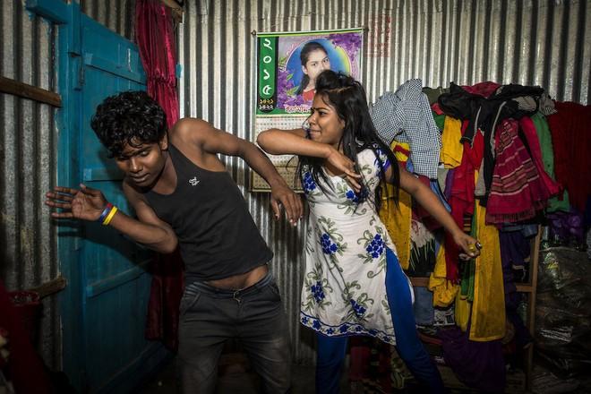 Priya đang trêu đùa một khách hàng bằng cách giả vờ đánh anh ta.