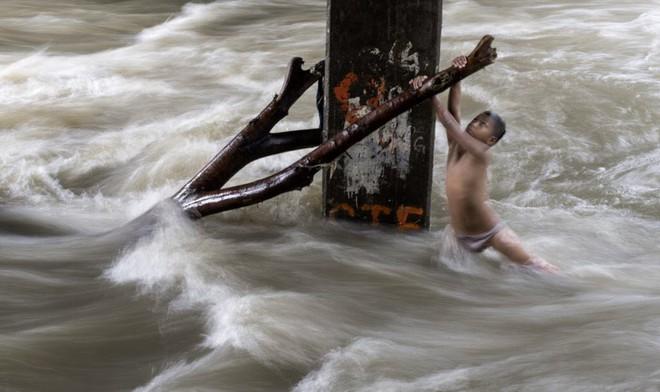 24h qua ảnh: Cậu bé mạo hiểm chơi dưới dòng nước chảy xiết ở Philippines - Ảnh 2.