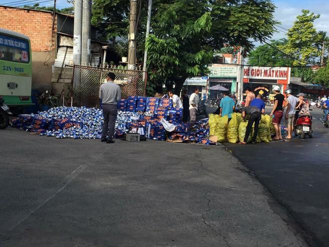 Người dân Bình Dương giúp tài xế gom hàng trăm thùng bia rơi xuống đường - Ảnh 2.