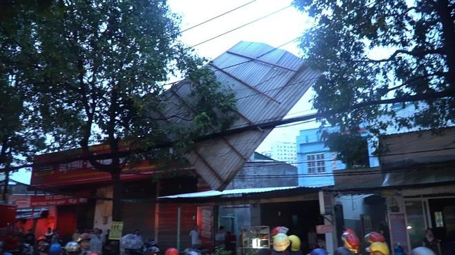 Người đi đường hốt hoảng khi tấm tôn 'khủng' bị gió thổi bay trên phố Sài Gòn - Ảnh 1.