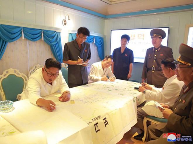Triều Tiên lần đầu công bố hình ảnh gây sốt: Nhà lãnh đạo Kim Jong-un dầm mưa đi thị sát - Ảnh 1.