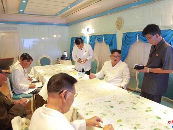 Triều Tiên lần đầu công bố hình ảnh gây sốt: Nhà lãnh đạo Kim Jong-un dầm mưa đi thị sát - Ảnh 2.