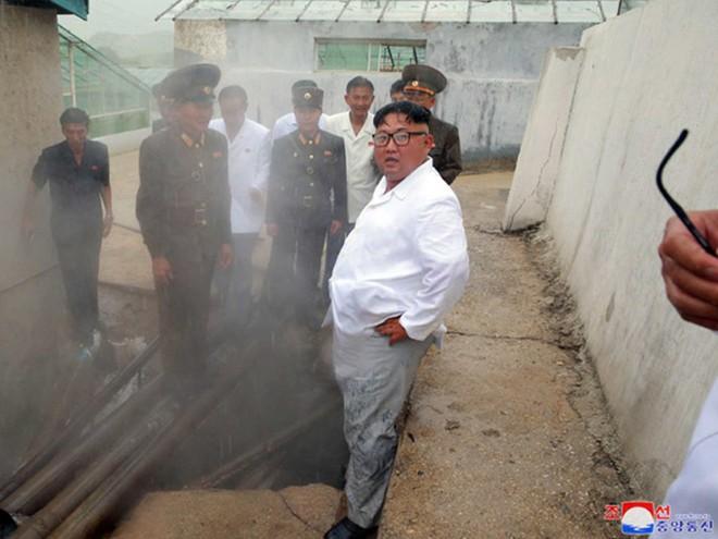 Triều Tiên lần đầu công bố hình ảnh gây sốt: Nhà lãnh đạo Kim Jong-un dầm mưa đi thị sát - Ảnh 5.