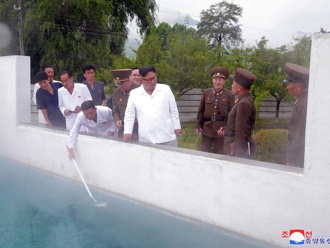 Triều Tiên lần đầu công bố hình ảnh gây sốt: Nhà lãnh đạo Kim Jong-un dầm mưa đi thị sát - Ảnh 6.