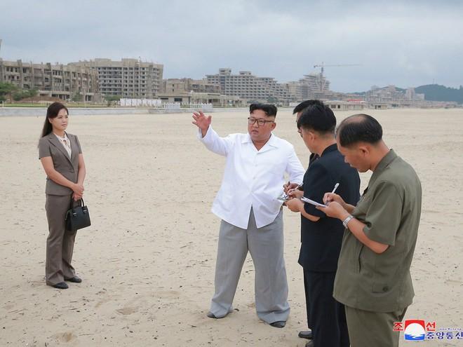 Triều Tiên lần đầu công bố hình ảnh gây sốt: Nhà lãnh đạo Kim Jong-un dầm mưa đi thị sát - Ảnh 7.