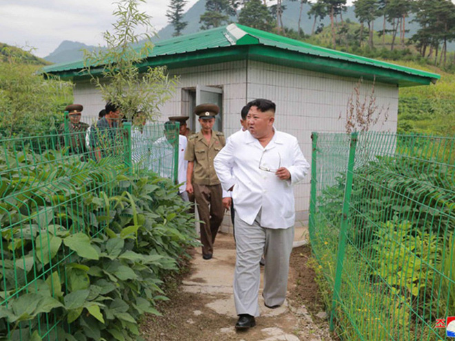 Triều Tiên lần đầu công bố hình ảnh gây sốt: Nhà lãnh đạo Kim Jong-un dầm mưa đi thị sát - Ảnh 8.