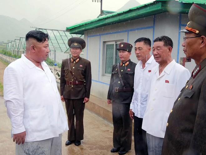 Triều Tiên lần đầu công bố hình ảnh gây sốt: Nhà lãnh đạo Kim Jong-un dầm mưa đi thị sát - Ảnh 10.