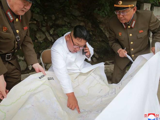 Triều Tiên lần đầu công bố hình ảnh gây sốt: Nhà lãnh đạo Kim Jong-un dầm mưa đi thị sát - Ảnh 12.