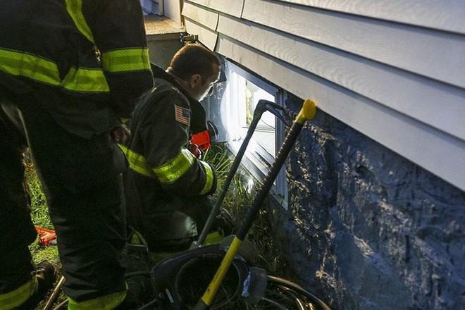 Lính cứu hỏa tìm cách vào một ngôi nhà qua cửa sổ tầng hầm để kiểm tra đường ống dẫn  gas  tại đây.