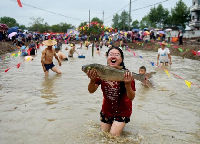 24h qua ảnh: Cá mắc cạn hàng loạt trên đường phố sau lũ lụt ở Mỹ - Ảnh 3.