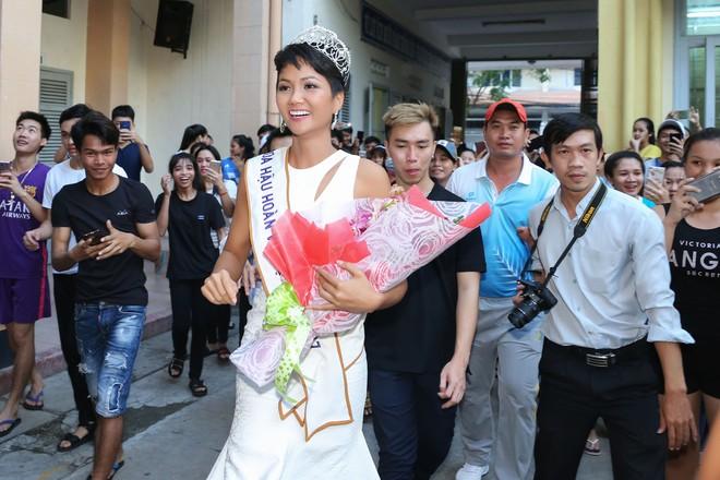 Hàng trăm sinh viên ùa tới khi hoa hậu HHen Niê về thăm trường cũ - Ảnh 1.