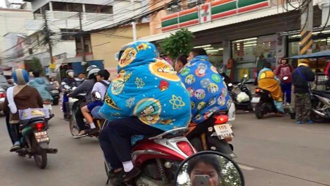 Bức hình thanh niên Bangkok trùm chăn lái xe máy đang được chia sẻ nhiều trên mạng xã hội.